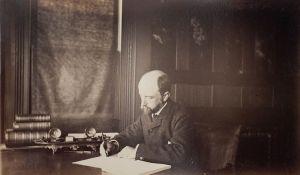 Henry_Adams_seated_at_desk_in_dark_coat,_writing,_photograph_by_Marian_Hooper_Adams,_1883